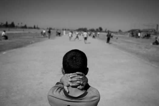 A young boy, whose role is to fetch stray balls, wraps his hands around his neck as he watches a long game of Pelota Mixteca.