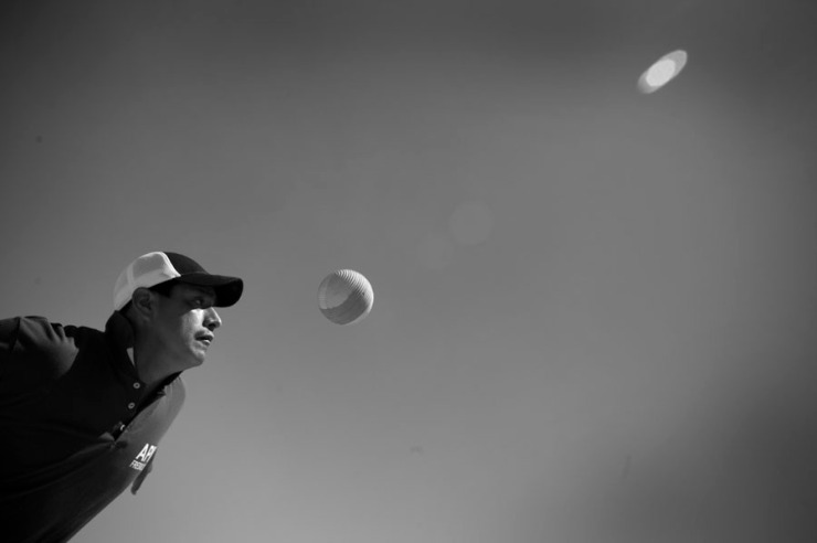 Adán Santiago fixes his gaze on the rubber ball as to not miss a hit during a game of Pelota Mixteca in Fresno, CA.