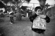 Children of farm workers show off the presents they recieved as part of a toy giveaway organized by the members of FIOB in Vista, CA.
