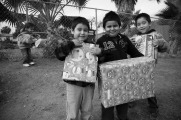 Children of farm workers show off the presents they recieved in a toy giveaway organized by the members of FIOB in Vista, CA.