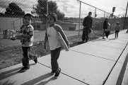 Children of farm workers head home after getting a present in a Christmas giveaway organized by members of FIOB in Vista, CA.