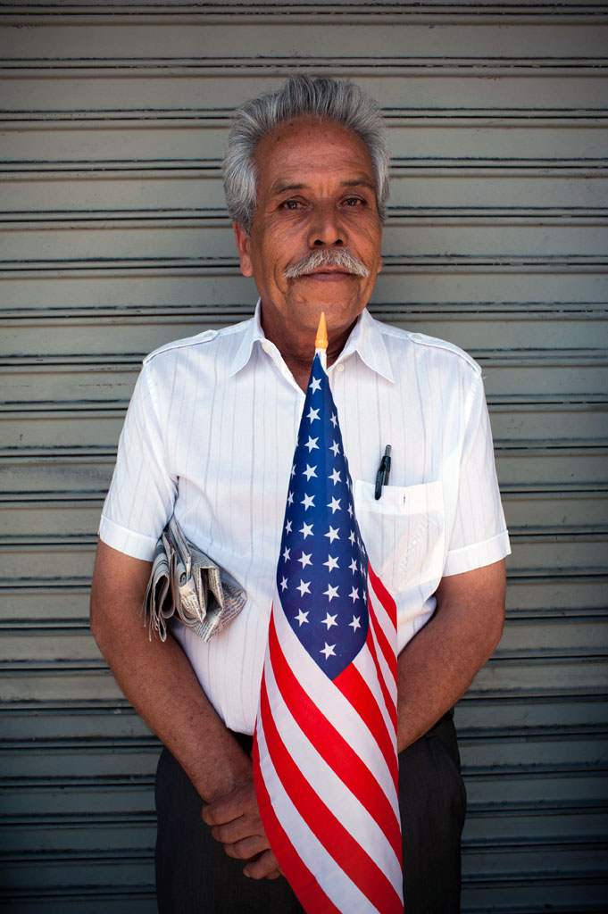 Aniceto Evarez holds an American flag as he waits to take part in a May Day Rally in Los Angeles. /LEOPOLDO PEÑA