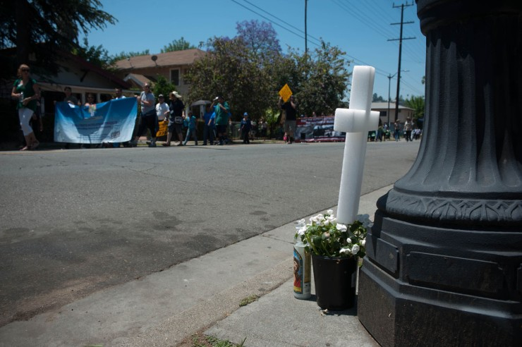 Particpantes de la Marcha de Paz pasan ante una cruz que marca el sitio donde murió un miembro de la comunidad del noreste de Los Angeles./LEOPOLDO PEÑA